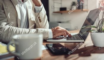 stock-photo-businessman-wearing-linen-suit-sitting-at-his-desk-and-using-laptop-in-the-office-1324138460