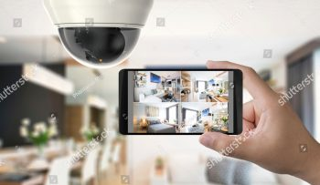 stock-photo-hand-holding-d-rendering-mobile-connect-with-security-camera-1038714985