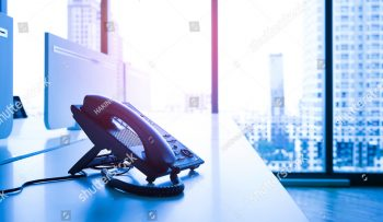 stock-photo-telephone-on-desk-with-big-window-city-view-modern-office-concept-531602569