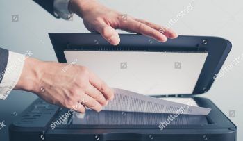 stock-photo-the-hands-of-a-young-businessman-is-placing-a-document-on-a-flatbed-scanner-in-preparation-for-264387707